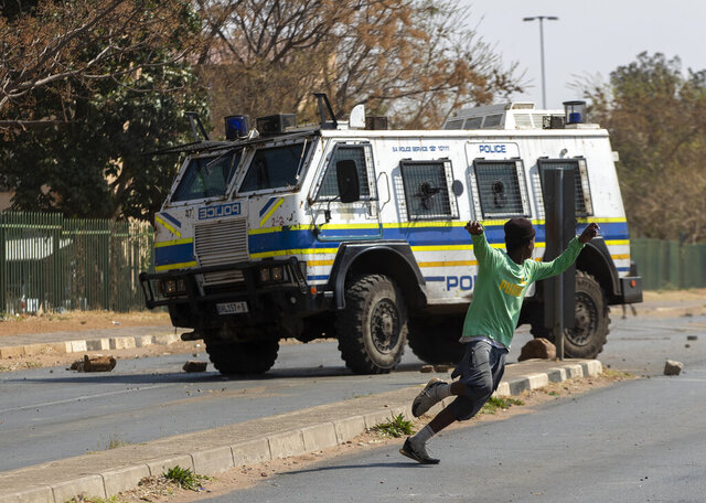 Protesters run for cover as they clash with police in Eldorado Park, Johannesburg, South Africa, Thursday, Aug. 27, 2020. Residents from the township, south of Johannesburg are demanding justice for a teenager shot and killed, allegedly at the hands of police Wednesday. (AP Photo/Themba Hadebe)