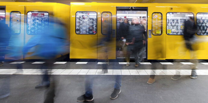 File -- In this Friday, Feb. 20, 2015 photo travellers leave a BVG subway train in Berlin, Germany. Berlin is unveiling a new app that will let people use public transport, rental bikes, car-sharing and taxis seamlessly to travel through the German capital. (Lukas Schulze/dpa via AP)