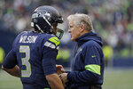Seattle Seahawks head coach Pete Carroll, right, talks with quarterback Russell Wilson, left, during the first half of an NFL football game against the Arizona Cardinals, Sunday, Dec. 22, 2019, in Seattle. (AP Photo/Elaine Thompson)
