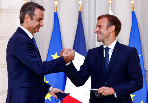 Greek Prime Minister Kyriakos Mitsotakis, left, and French President Emmanuel Macron shake hands after the signing of a new defense deal at The Elysee Palace Tuesday, Sept. 28, 2021 in Paris. France and Greece announced on Tuesday a major, multibillion-euro defense deal including Athens' decision to buy three French warships. (Ludovic Marin, Pool Photo via AP)