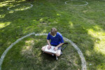 FILE - In this Aug. 25, 2020, file photo, Logan Armstrong, a junior, works while sitting inside a painted circle on the lawn of the Oval during the first day of fall classes at Ohio State University in Columbus, Ohio. Officials in college towns all over the U.S. are fretting that off-campus students are being counted in places other than the communities where their schools are located.  (Joshua A. Bickel/The Columbus Dispatch via AP, File)