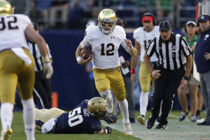 Notre Dame quarterback Ian Book (12) tries to stay in bounds as Navy linebacker Paul Carothers defends during the first half of an NCAA college football game Saturday, Oct. 27, 2018, in San Diego. (AP Photo/Gregory Bull)