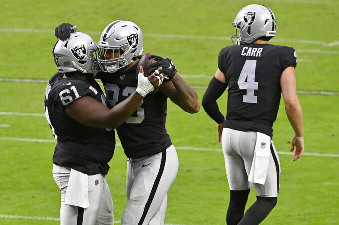 Las Vegas Raiders center Rodney Hudson (61) celebrates with tight end Darren Waller (83) after Waller scored a touchdown against the Tampa Bay Buccaneers during the second half of an NFL football game, Sunday, Oct. 25, 2020, in Las Vegas. (AP Photo/David Becker)