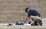 FILE - In this Friday, July 20, 2012 file photo, an investigator inspects evidence outside the Century 16 movie theater east of the Aurora Mall in Aurora, Colo. A gunman in a gas mask barged into the crowded Denver-area theater during a midnight showing of the Batman movie, hurled a gas canister and then opened fire in one of the deadliest mass shootings in recent Colorado history. On Monday, June 29, 2020, the Colorado Supreme Court upheld the state's ban on large capacity gun magazines, a law put into effect a year after the mass shooting in the Aurora theatre. (AP Photo/David Zalubowski, File)