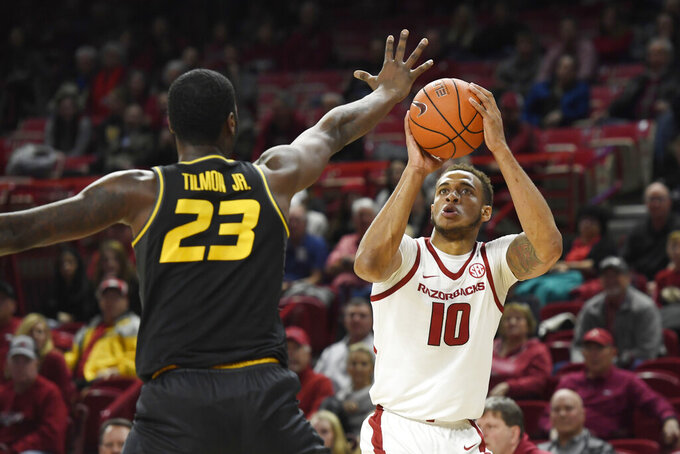 FILE - In this Wednesday, Jan. 23, 2019 file photo, Arkansas forward Daniel Gafford (10) shoots over Missouri defender Jeremiah Tilmon (23) during the first half of an NCAA college basketball game, Wednesday, Jan. 23, 2019, in Fayetteville, Ark. Tennessee forward Grant Williams is the Associated Press' Southeastern Conference player of the year and Mississippi's Kermit Davis is coach of the year. Williams earned unanimous first-team all-SEC honors for a second straight season. The 14-member media panel also voted Arkansas' Daniel Gafford, Kentucky's PJ Washington, LSU's Tremont Waters and Mississippi State's Quinndary Weatherspoon to the first team(AP Photo/Michael Woods, File)