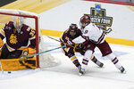 Massachusetts' Bobby Trivigno (8) sends the puck past Minnesota Duluth goaltender Zach Stejskal (35), before Garrett Wait, not seen, knocked it in for an overtime goal in an NCAA men's Frozen Four hockey semifinal in Pittsburgh, early Friday, April 9, 2021. Massachusetts won 3-2 and will face St. Cloud State in the championship game Saturday. (AP Photo/Keith Srakocic)