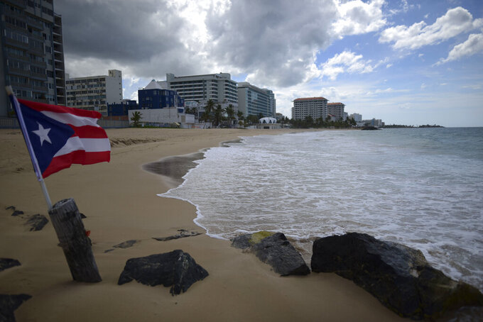 FILE - In this May 21, 2020 file photo, a Puerto Rican flag flies on an empty beach at Ocean Park, in San Juan, Puerto Rico. The number of tourists arrested in Puerto Rico on charges of violating COVID-19 measures is increasing as the U.S. territory cracks down on visitors who stay out past curfew and refuse to wear face masks or remain under quarantine, authorities said Tuesday, March 23, 2021. (AP Photo/Carlos Giusti, File)