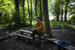 Activist Salome Dorfer sits on a bench inside the Luetzerath forest, Germany, Tuesday, July 20, 2021. Activists try to stop the village being evicted as a result of the the construction of a coal mine. (AP Photo/Bram Janssen)