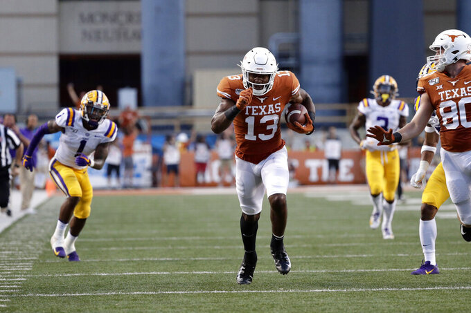 Texas wide receiver Brennan Eagles (13) runs with a touchdown reception in front of LSU cornerback Kristian Fulton, left, during the first half of an NCAA college football game Saturday, Sept. 7, 2019, in Austin, Texas. (AP Photo/Eric Gay)