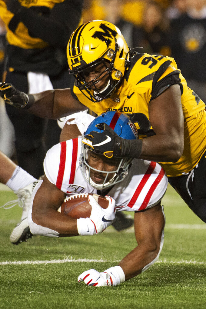 Mississippi running back Snoop Conner, bottom, is tackled by Missouri defensive lineman Tre Williams, top, during the second quarter of an NCAA college football game Saturday, Oct. 12, 2019, in Columbia, Mo. (AP Photo/L.G. Patterson)