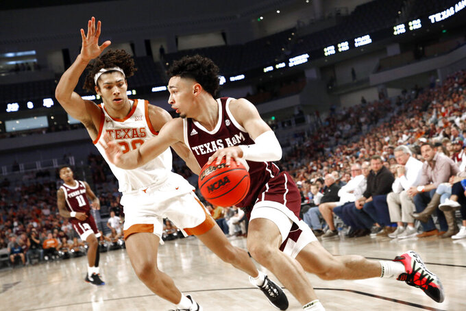 Texas A&M guard Andre Gordon (20) drives inside as Texas forward Jericho Sims (20) defends during the first half of an NCAA college basketball game, Sunday, Dec. 8, 2019, in Fort Worth, Texas. (AP Photo/Ron Jenkins)