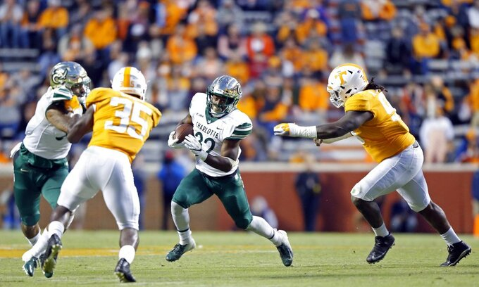 Charlotte running back Benny LeMay (32) runs for yardage as he's chased by Tennessee linebacker Jonathan Kongbo (99) in the second half of an NCAA college football game Saturday, Nov. 3, 2018, in Knoxville, Tenn. Tennessee won 14-3. (AP Photo/Wade Payne)