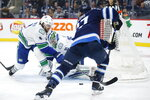 Vancouver Canucks goaltender Thatcher Demko (35) saves the shot from Winnipeg Jets' Nikolaj Ehlers (27) as Christopher Tanev (8) defends during the second period of an NHL hockey game, Friday, Nov. 8, 2019 in Winnipeg, Manitoba. (John Woods/Canadian Press via AP)