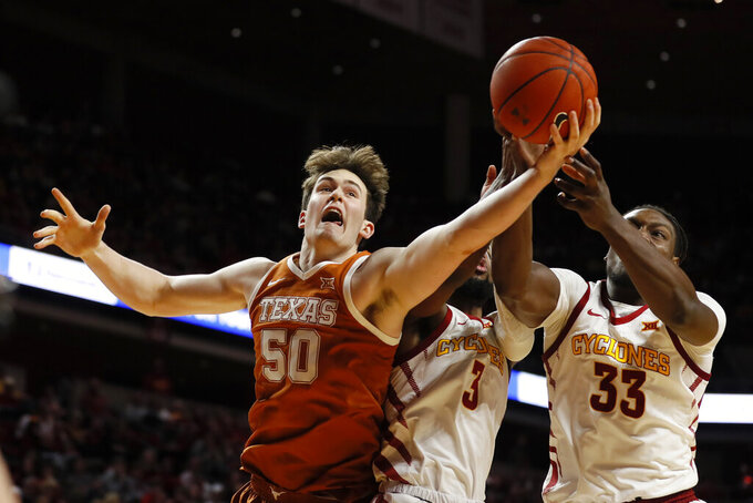 Texas center Will Baker (50) fights for a rebound with Iowa State's Tre Jackson (3) and Solomon Young, right, during the second half of an NCAA college basketball game, Saturday, Feb. 15, 2020, in Ames, Iowa. (AP Photo/Charlie Neibergall)