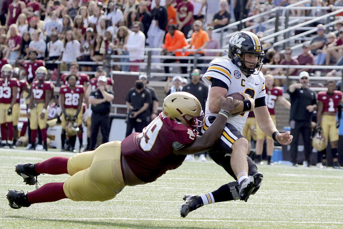 Missouri quarterback Connor Bazelak (8) slides for extra yardage as Boston College defensive tackle TJ Rayam (99) dives to make the tackle during the second half of an NCAA college football game, Saturday, Sept. 25, 2021, in Boston. (AP Photo/Mary Schwalm)