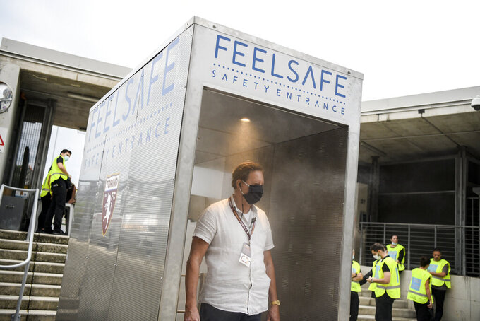 """A man passes through an anti COVID-19 automatic gate meant to speed up checks at the entrance of the Grande Torino stadium in Turin, Italy, where the Italian Serie A soccer match between Torino and Verona is taking place Wednesday, July 22, 2020. The device, dubbed """"Feel Safe"""" has a face recognition scanner which also reads the body temperature, before spraying a safe disinfectant on match goers. The device is being tested but the match is still taking place in a closed stadium. (Marco Alpozzi/LaPresse via AP)"""