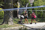 A woman with a stroller reacts as she and another woman pass through an area damaged by winds from Tropical Storm Isaias, Wednesday, Aug. 5, 2020, in the Queens borough of New York. A tree toppled onto a house and blocked the entrance to an adjacent home downing power lines as it fell. Residents said a local bus route was also affected. (AP Photo/Kathy Willens)