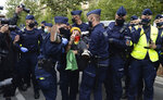 Polish police carry protesting environmentalists to the side to clear passage down one of Warsaw's main streets in Warsaw, Poland, Monday, Sept. 7, 2020. The Polish chapter of the international environmental group Extinction Rebellion blocked the street to spur the government into better protection of the environment, in a second such action in two days, in Warsaw. (AP Photo/Czarek Sokolowski)