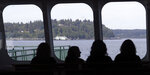 In this photo taken Wednesday, May 15, 2019, passengers sit behind windows at the front of a ferry boat as it approaches Vashon Island, Wash. An idyllic island near Seattle known for its counterculture lifestyle and low immunization rates is seeing an increase in the number of children vaccinated for measles and other diseases. Advocates attribute the rising vaccination numbers on Vashon Island to increasingly visible pro-vaccine information, expanded access to shots and media coverage of measles outbreaks in the Pacific Northwest and New York this year. (AP Photo/Elaine Thompson)