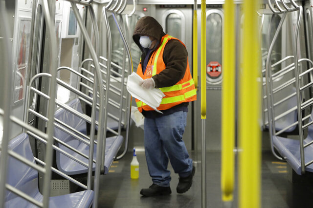 FILE- In this May 5, 2020 file photo a New York Metropolitan Transportation authority worker worker disinfects a subway train at the Coney Island Stillwell Avenue Terminal, in the Brooklyn borough of New York. New York City appears to be on track to begin loosening restrictions in June, but residents who don't yet feel comfortable commuting by subway may have to improvise, NYC Mayor Bill de Blasio said Friday, May 29, 2020. (AP Photo/Frank Franklin II, File)