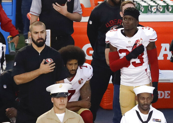 FILE - In this Thursday, Sept. 1, 2016 file photo, San Francisco 49ers quarterback Colin Kaepernick, middle, kneels during the national anthem before the team's NFL preseason football game against the San Diego Chargers, in San Diego. When Kaepernick took a knee during the national anthem to take a stand against police brutality, racial injustice and social inequality, he was vilified by people who considered it an offense against the country, the flag and the military. Nearly four years later, it seems more people are starting to side with Kaepernick's peaceful protest and now are calling out those who don't understand the intent behind his action. (AP Photo/Chris Carlson, File)