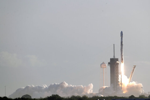 A Falcon 9 SpaceX rocket with a payload of approximately 60 satellites for SpaceX's Starlink broadband network lifts off from pad 39A at the Kennedy Space Center in Cape Canaveral, Fla., Wednesday, March 18, 2020. (AP Photo/John Raoux)