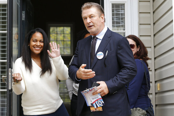 Actor Alec Baldwin, center, points out a throng of media as he talks to Kristin Goodlett as he walks with Amanda Pohl, candidate for Virginia Senate District 11 in her neighborhood in Midlothian, Va., Tuesday, Oct. 22, 2019. Baldwin campaigned for several candidates around the state. (AP Photo/Steve Helber)