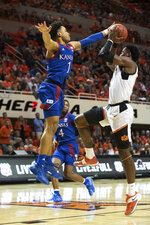 Kansas guard Devon Dotson (1) reaches to block a shot by Oklahoma State's Cameron McGriff, as Kansas guard Isaiah Moss (4) watches during the second half of an NCAA college basketball game in Stillwater, Okla., Monday, Jan. 27, 2020. Kansas defeated Oklahoma State 65-50. (AP Photo/Brody Schmidt)