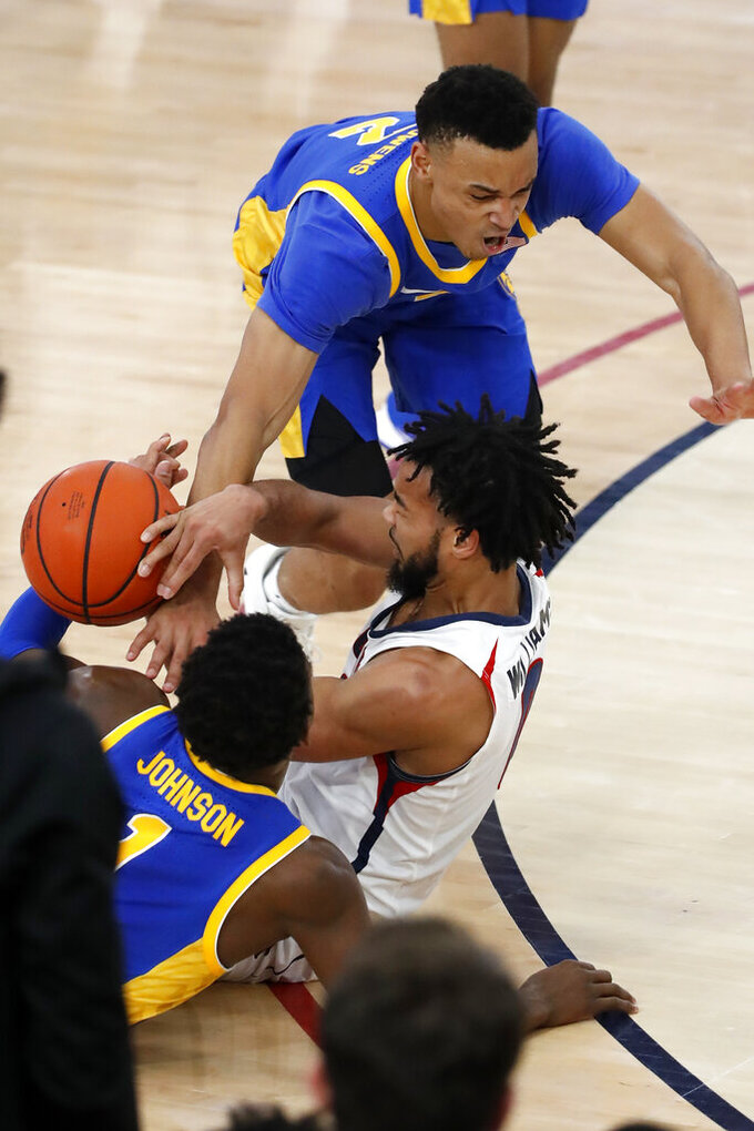 Robert Morris' Josh Williams, center, competes for the ball against Pittsburgh's Trey McGowens, top, and Xavier Johnson during the second half of an NCAA college basketball game in Pittsburgh, Tuesday, Nov. 12, 2019. Pittsburgh won 71-57. (AP Photo/Gene J. Puskar)