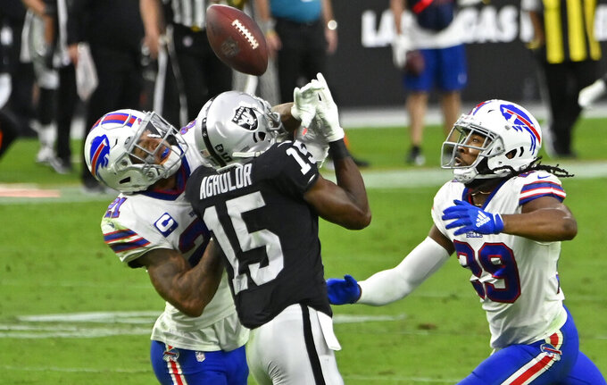 Buffalo Bills free safety Jordan Poyer, left, and cornerback Josh Norman, right, guard Las Vegas Raiders wide receiver Nelson Agholor (15) during the second half of an NFL football game, Sunday, Oct. 4, 2020, in Las Vegas. Poyer was called for pass interference on the play. (AP Photo/David Becker)