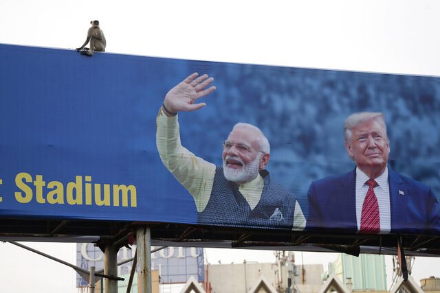FILE- In this Feb. 19, 2020, file photo, a monkey sits on a hoarding welcoming U.S. President Donald Trump ahead of his visit to Ahmedabad, India. A festive mood has enveloped Ahmedabad in India's northwestern state of Gujarat ahead of Prime Minister Narendra Modi's meeting Monday with U.S. President Donald Trump, whom he's promised millions of adoring fans. The rally in Modi's home state may help replace his association with deadly anti-Muslim riots in 2002 that landed him with a U.S. travel ban. It may also distract Indians, at least temporarily, from a slumping economy and ongoing protests over a citizenship law that excludes Muslims, but also risks reopening old wounds. (AP Photo/Ajit Solanki, File)