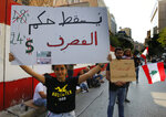 Anti-government protesters hold placards, one reads,