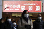 People wearing face masks make their way near a station in Osaka, western Japan Wednesday, Jan. 13, 2021. The sign, top left, reads