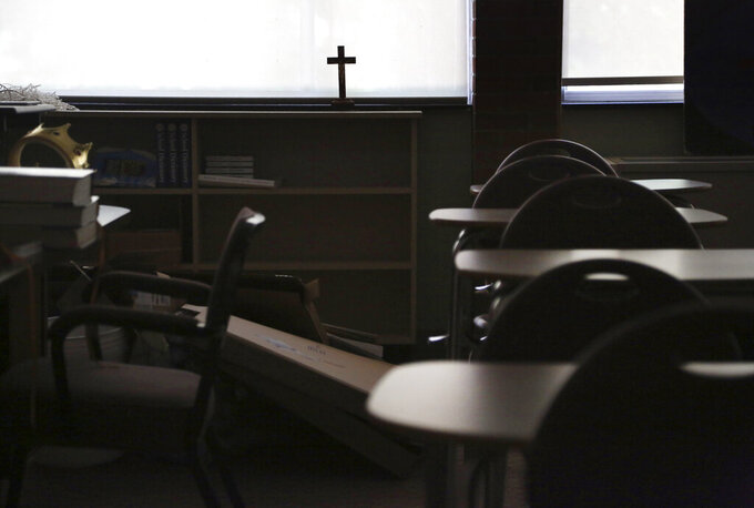 FILE - In this Monday, June 8, 2020 file photo, a cross sits in the window of an empty classroom at Quigley Catholic High School in Baden, Pa. On Monday, Feb. 8, 202, Catholic education officials reported that enrollment in Roman Catholic schools in the United States dropped 6.4% from the previous academic year amid the pandemic and economic stresses — the largest single-year decline in at least five decades. (AP Photo/Jessie Wardarski)