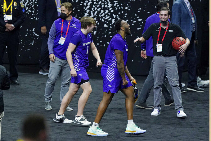 Abilene Christian's Airion Simmons, second from right, and Logan McLaughlin (1) leave the court after Abilene Christian upset Texas 53-52 in a college basketball game in the first round of the NCAA tournament at Lucas Oil Stadium in Indianapolis Sunday, March 21, 2021. (AP Photo/Mark Humphrey)