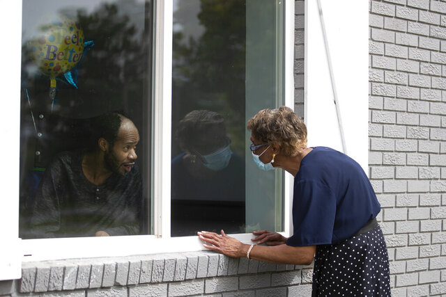 Southern Pines nursing home resident Wayne Swint gets a birthday visit from his mother, Clemittee Swint, in Warner Robins, Ga., on Friday, June 26, 2020. Face to face visits are not allowed but staff members help arrange window visits. (AP Photo/John Bazemore)