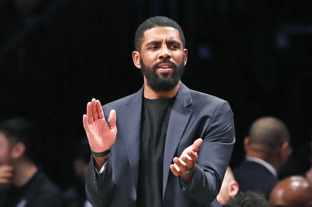 "FILE - In this Tuesday, Jan. 7, 2020, file photo, injured Brooklyn Nets guard Kyrie Irving applauds his teammates from the bench during the first half of an NBA basketball game against the Oklahoma City Thunder, in New York. Irving is joining rapper Common and others for a TV special calling for action following the death of Breonna Taylor. Irving is producing ""#SAYHERNAME: BREONNA TAYLOR,"" which will debut Wednesday, July 8, 2020, at 7 p.m. EDT on the PlayersTv digital and broadcast network.(AP Photo/Kathy Willens, File)"