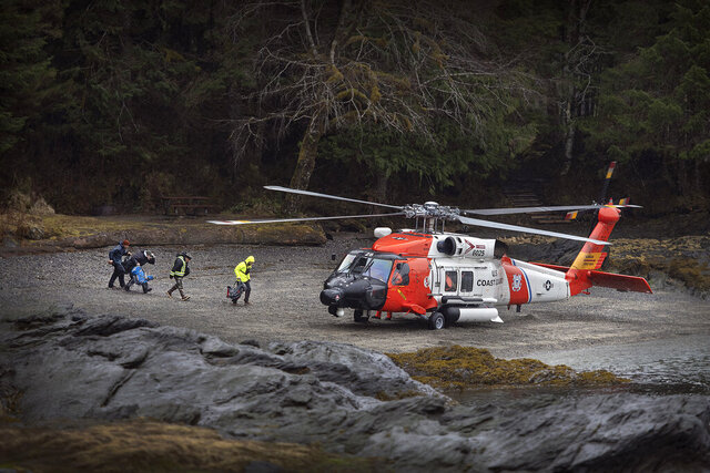 A U.S. Coast Guard helicopter sits in a beach area in order to airlift personnel with Ketchikan Volunteer Rescue Squad to a remote area of Lunch Creek in the search for a missing boy, Saturday, March 28, 2020, at a state recreation site in Ketchikan, Alaska. A search continued into Saturday morning for a 5-year-old boy reported missing on Lunch Creek Trail. Jaxson Brown and his mother, Jennifer Treat, set out for a hike Wednesday afternoon, but became disoriented and lost the trail. They spent the night together, and in the morning Treat left Jaxson to seek help on her own. In her own search, Treat suffered a serious injury to her leg. Treat was located 3 miles up the trail and airlifted off the trail by helicopter late Thursday afternoon. On Friday, searchers found a shoe that belonged to the boy. (Dustin Safranek/Ketchikan Daily News via AP)