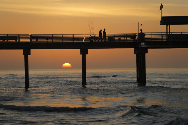 In this March 13, 2020, photo, people walk on a pier with their fishing poles at dawn in Orange Beach, Ala. As oil spewed into the Gulf of Mexico from a blown-out BP well in 2010, residents wondered whether their home would ever be the same. The Deepwater Horizon disaster changed the region, with a flood of spending altering landscapes and attitudes. (AP Photo/Gerald Herbert)