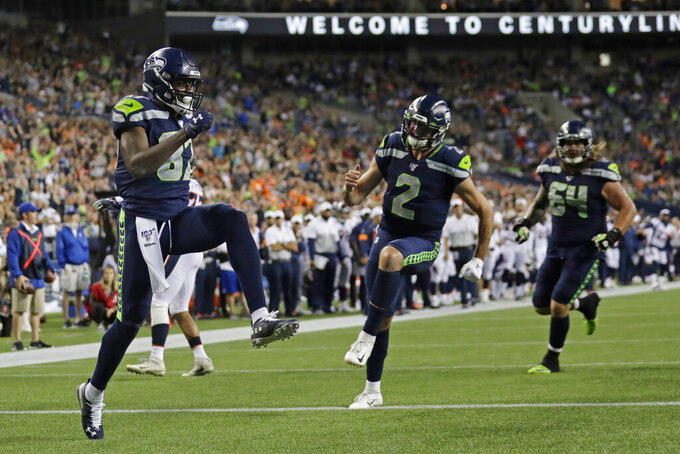 Seattle Seahawks wide receiver Jazz Ferguson, left, celebrates after he caught a pass from quarterback Paxton Lynch (2) to score a touchdown against the Denver Broncos during the second half of an NFL football preseason game Thursday, Aug. 8, 2019, in Seattle. (AP Photo/Stephen Brashear)