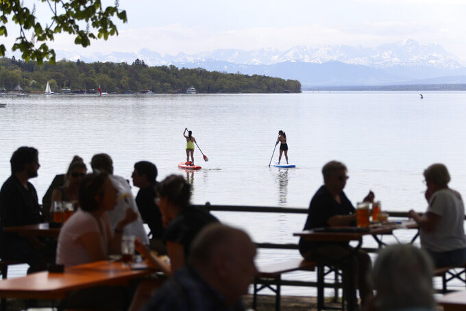 Stand-up paddler make their way while people enjoy the sunny weather on the re-opening day of beer gardens, following the lifting of measures to avoid the spread of the corona virus, at lake 'Ammersee' in front of the alps in Inning, Germany, Monday, May 10, 2021. (AP Photo/Matthias Schrader)