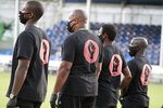 Members of all the MLS soccer teams march around the stadium before a match Wednesday, July 8, 2020, in Kissimmee, Fla., while wearing shirts and masks with messages about race. (AP Photo/John Raoux)