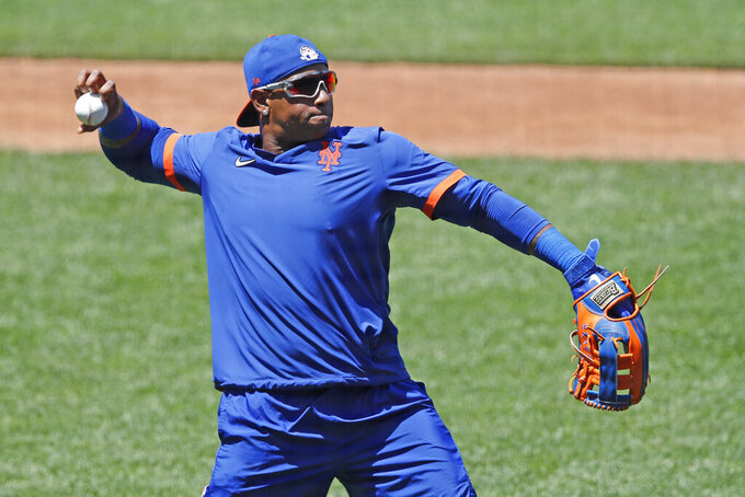 New York Mets left fielder Yoenis Cespedes stretches out to throw the ball as he waits for his turn in the batting cage during the afternoon session of a summer baseball training camp workout at Citi Field, Thursday, July 9, 2020, in New York. (AP Photo/Kathy Willens)