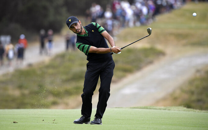 International team player Abraham Ancer of Mexico plays his second shot on the 6th hole in his singles match during the President's Cup golf tournament at Royal Melbourne Golf Club in Melbourne, Sunday, Dec. 15, 2019. (AP Photo/Andy Brownbill)