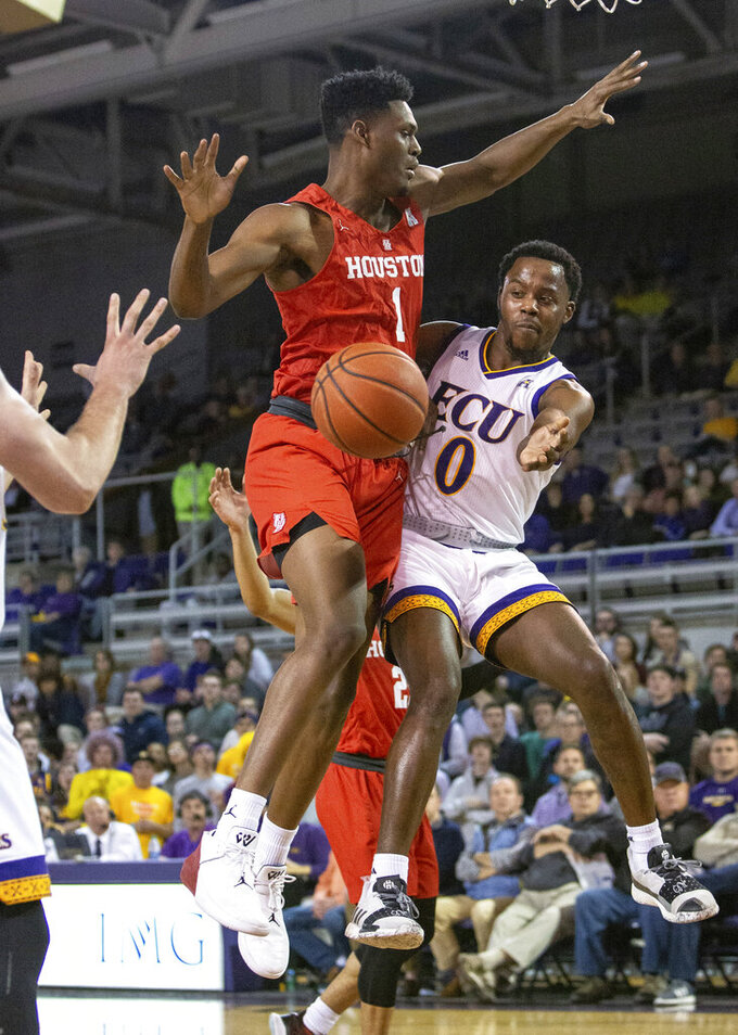 East Carolina's Isaac Fleming (0) passes around Houston's Chris Harris Jr. (1) during the first half of an NCAA college basketball game in Greenville, N.C., Wednesday, Feb. 27, 2019. (AP Photo/Ben McKeown)
