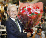 Akira Yoshino of Asahi Kasei Corporation poses with a bouquet of flowers in Tokyo Wednesday, Oct. 9, 2019, following an announcement that he was awarded the Nobel Prize in Chemistry. The prize went to John B. Goodenough of the University of Texas; M. Stanley Whittingham of the State University of New York at Binghamton; and  Yoshino. (Yuta Omori/Kyodo News via AP)