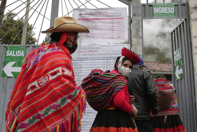 Voters wearing masks to curb the spread of COVID-19 line up at a polling post during general elections in Ollantaytambo, Peru, Sunday, April 11, 2021. (AP Photo/Sharon Castellanos)