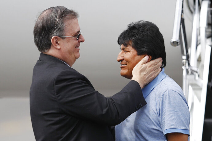 In this Tuesday, Nov. 12, 2019 photo, Mexican Foreign Minister Marcelo Ebrard, left, welcomes former Bolivian President Evo Morales upon his arrival to Mexico City. Mexico granted asylum to Morales, who resigned on Nov. 10 under mounting pressure from the military and the public after his re-election victory triggered weeks of fraud allegations and deadly protests. (AP Photo/Eduardo Verdugo)