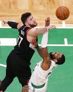 Portland Trail Blazers center Jusuf Nurkic, left, blocks a shot by Boston Celtics guard Kyrie Irving, right, during the second half of an NBA basketball game, Wednesday, Feb. 27, 2019, in Boston. (AP Photo/Mary Schwalm)
