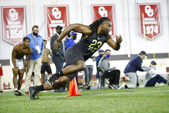 FILE - Oklahoma running back Rhamondre Stevenson participates in the school's Pro Day football workout for NFL scouts in Norman, Okla., in this Friday, March 12, 2021, file photo. The coronavirus pandemic scuttled the annual NFL scouting combine in Indianapolis, leaving prospects to show off for scouts, coaches and general managers at their college pro day instead. While players lamented the lost opportunity to gather in Indy to be poked, prodded, timed and tested — and to square off against their peers — an invitation was still a golden ticket. (AP Photo/Alonzo Adams, FILE)
